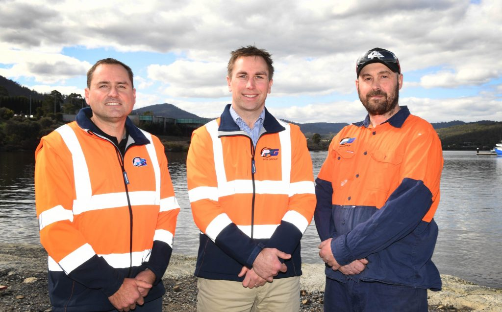 Three Hobart boat builders standing by the water smiling.